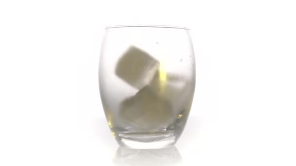 Ledové kostky padají do skla na černém pozadí. Zpomal. Koncept koktejlu
