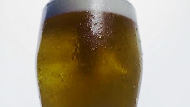 Finom buborékok emelkednek üvegben, fehér hátterű sörrel. Egy pohár sör közelről habos lassított felvételekkel.