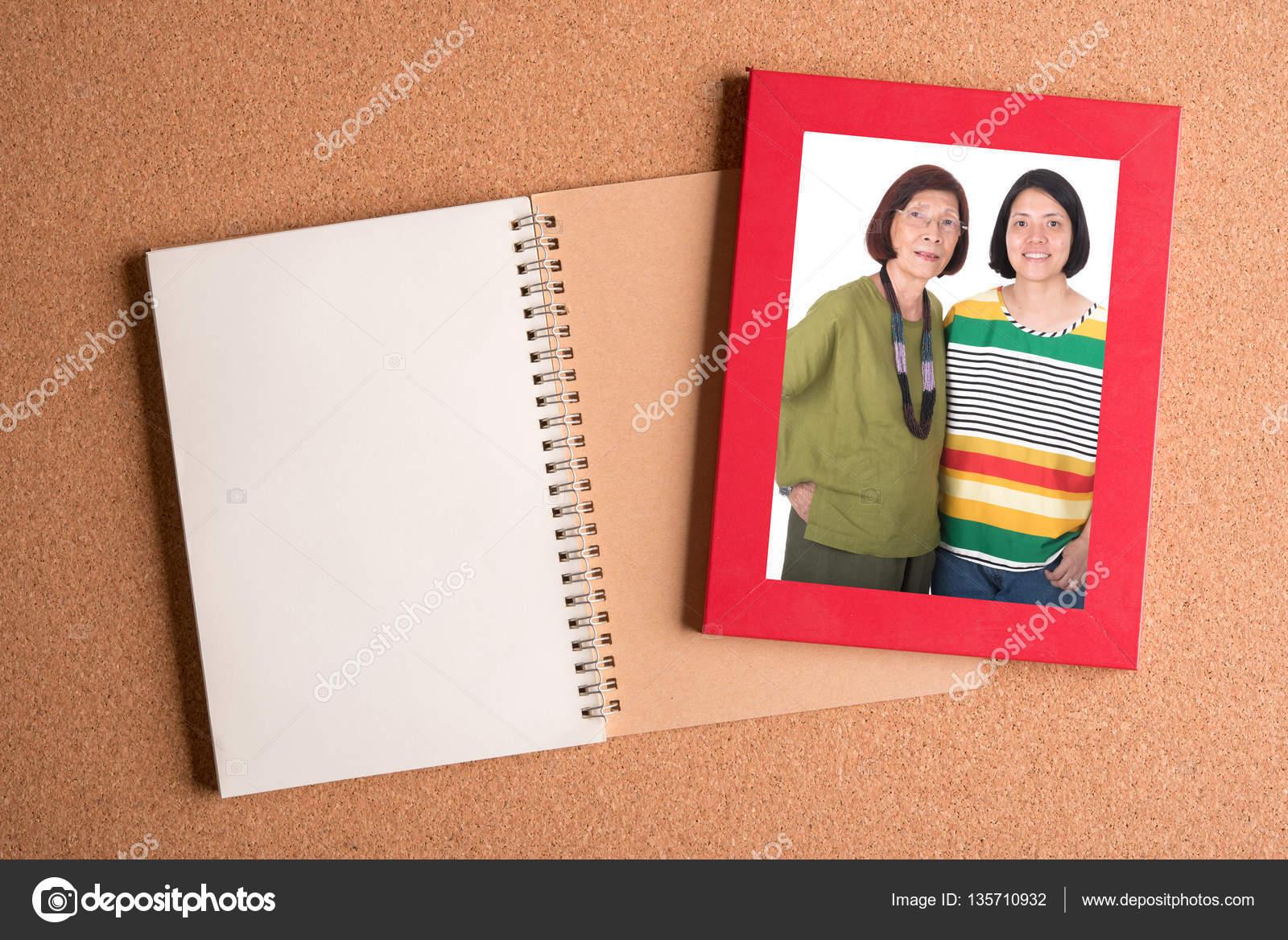 Notizbuch und Rahmen mit Bild von Mutter und Tochter auf Holz ...