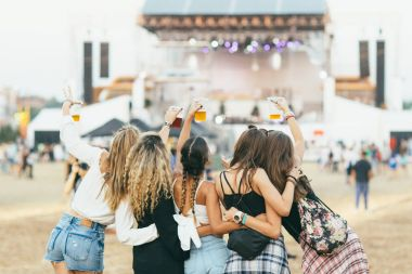 Friends drinking beer  at music festival