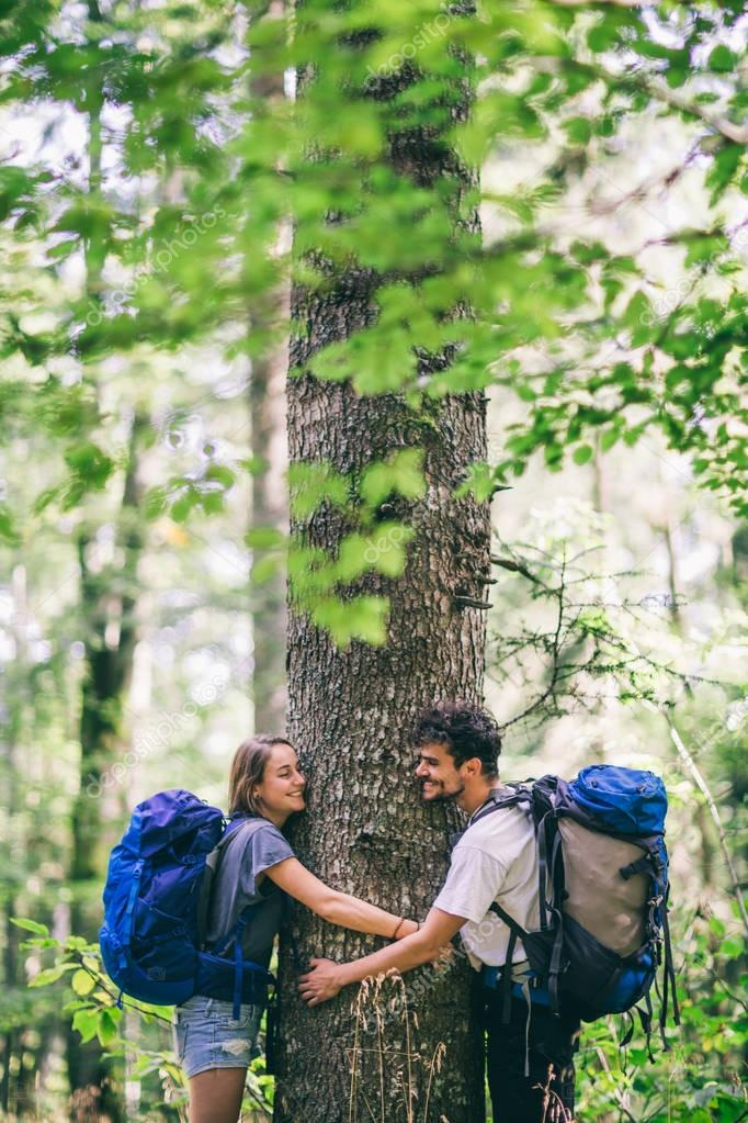 couple with backpacks hugging tree