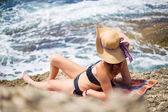 Mladá dívka v bikinách a slaměný klobouk na pláži se těší