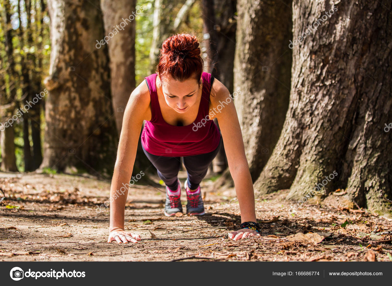 A girlfriend of a good body, doing pushups in the nature after a