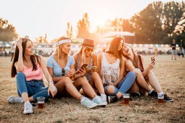 happy girlfriends enjoying start of the weekend on music festival