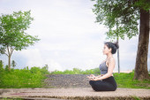 Young woman practicing yoga Everyday Yoga helps in concentration, breath, shape body, strength, help skin brighten. Among the Dharma Air in bright days