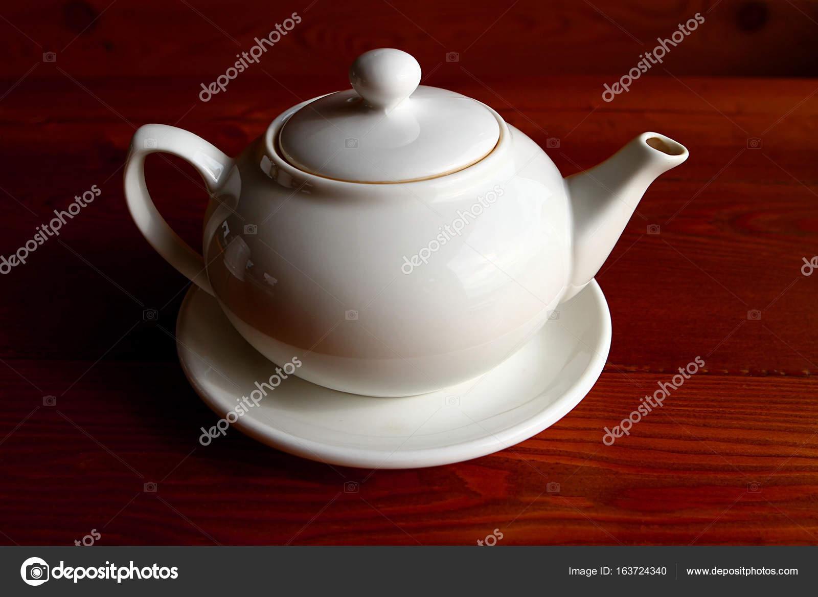 Weiße Teekanne weiße teekanne und die untertasse auf dem holztisch allein