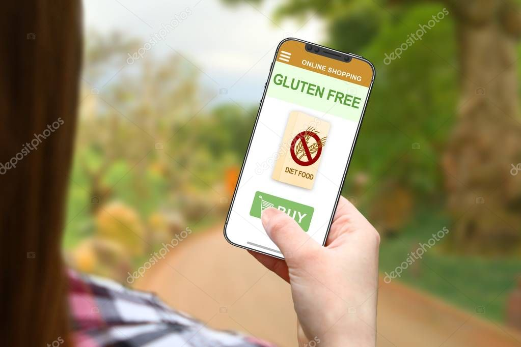 Gluten free diet idea, girl with frameless phone on blurred nature background