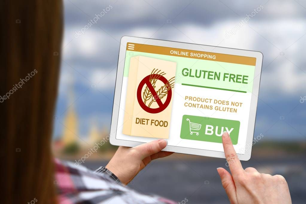 Gluten free diet concept, girl holds the digital tablet on blurred clouds background