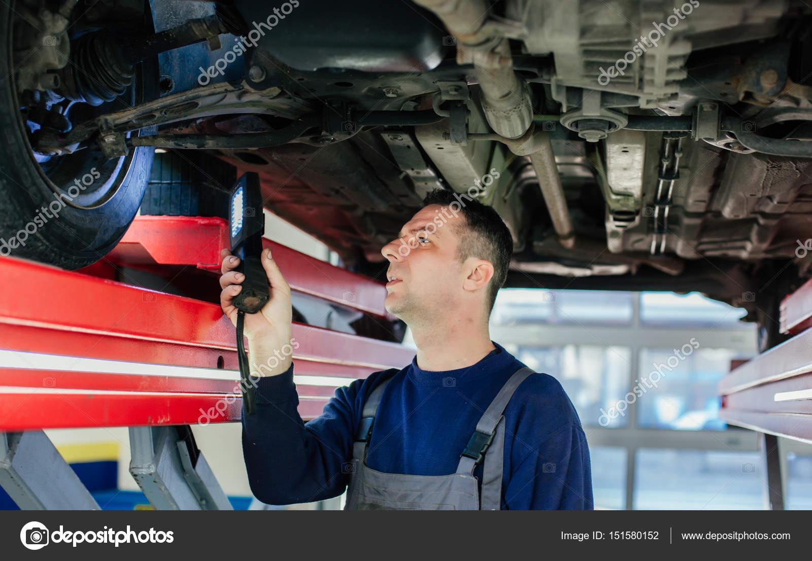 mechanic examining car using flashlight stock photo cokapoka