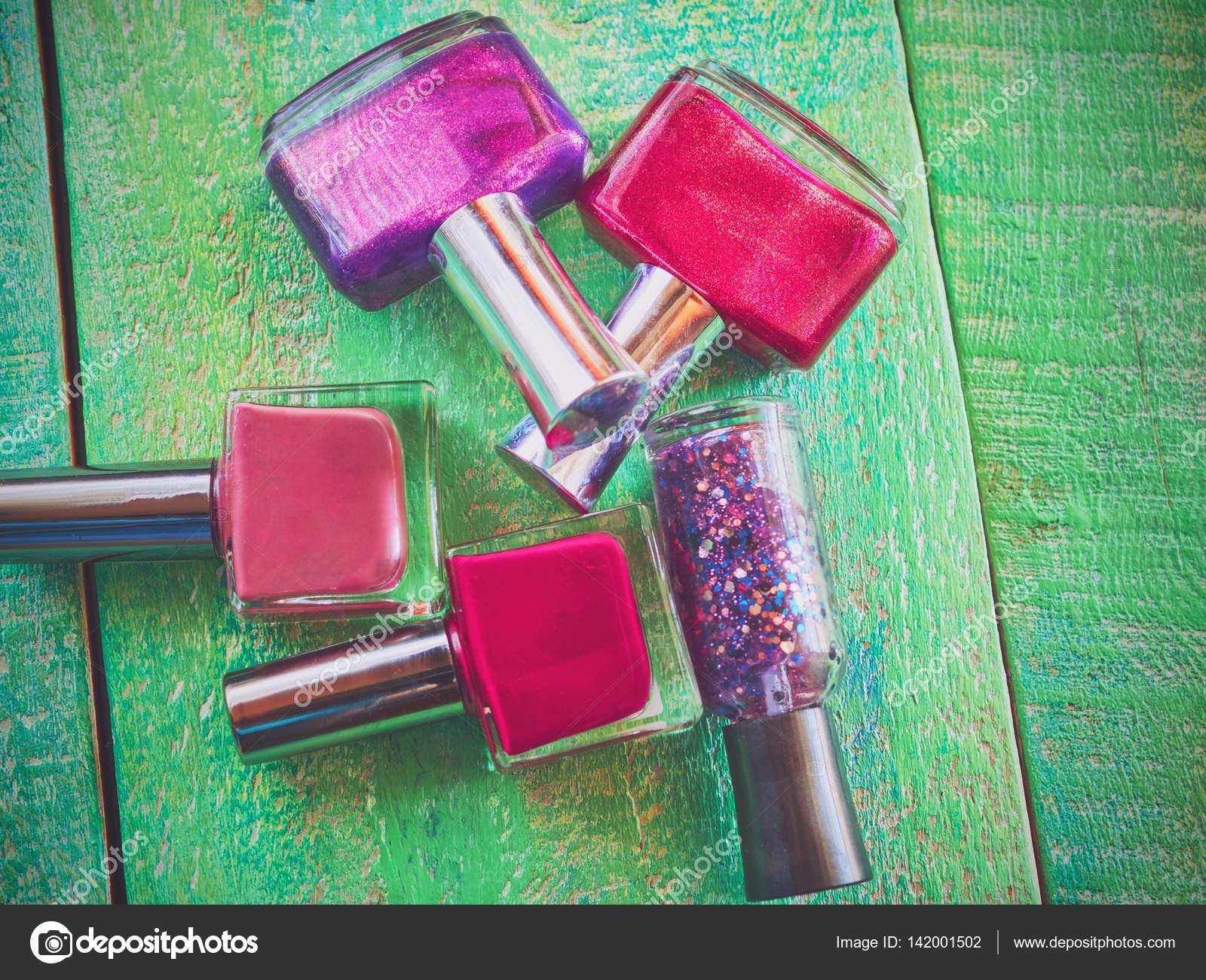 Grupo de esmaltes de uñas brillantes, sobre fondo color madera ...