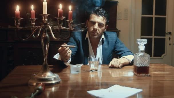 Muž kouří doutník u stolu