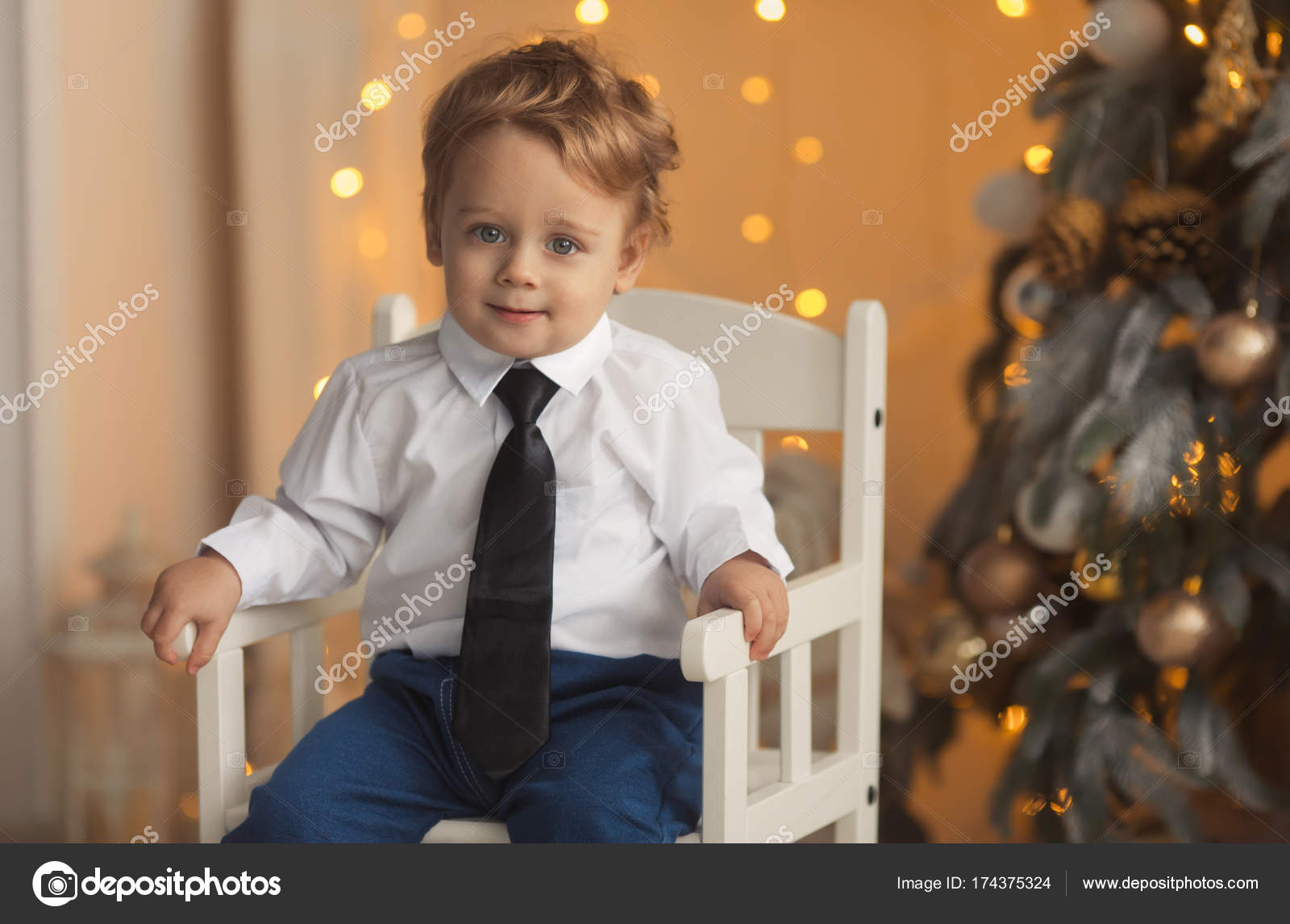 happy little boy sitting luxury decorated christmas tree gold colors