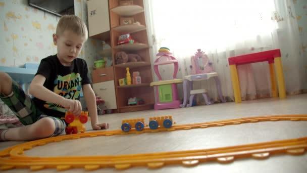 malý chlapec hraje s hračkou železnice ve herně