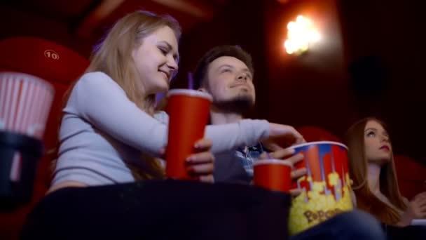 Glückliches Paar sitzt im Kino, schaut 3D-Film, isst Popcorn, lächelt.