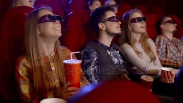 junge Leute sehen Filme im Kino, sehen eine Komödie in 3D, alle lächeln und essen Popcorn.