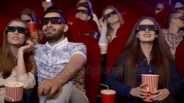 Freunde im Kino sehen einen faszinierenden Film in 3D-Gläsern, trinken Cola und essen Popcorn.