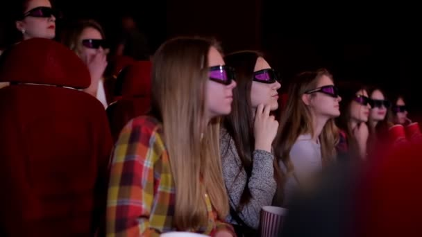 Young girls in glasses watch movies in cinema, watch in 3D.