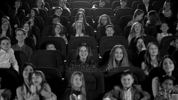 Šťastné děti v kině pohledu kreslený film. Černá a bílá