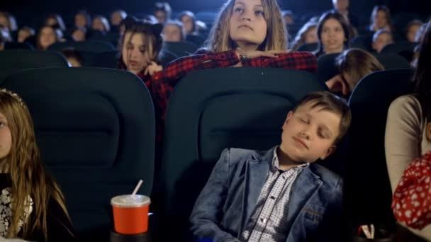 Álmos fiú féltem a moziban. a gyerekek nézni a nagy képernyőn egy rajzfilm.
