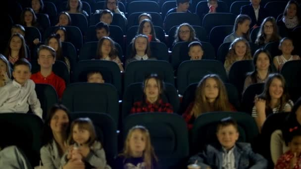 Video frames at the cinema with funny kids, who watch cartoon.