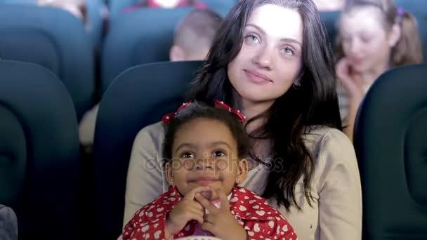 Boldog fiatal anya és a lánya költeni a moziban szabadidejükben.