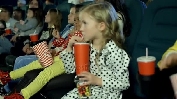 little girls watching animated cartoon and eating popcorn at the cinema.
