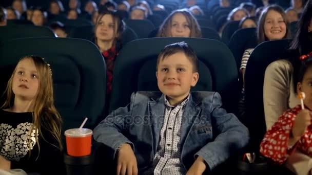Szép fiú, és sok kis lány film a moziban. Közelről portré.