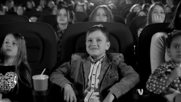 schöner Junge und viele kleine Mädchen, die Film im Kino anschauen. Porträt aus nächster Nähe. Schwarz-Weiß-Aufnahme.