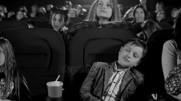 Schwarz-Weiß-Aufnahmen. Schläfriger Junge mit Angst im Kino. Kinder sehen Zeichentrickfilm auf der Großleinwand.