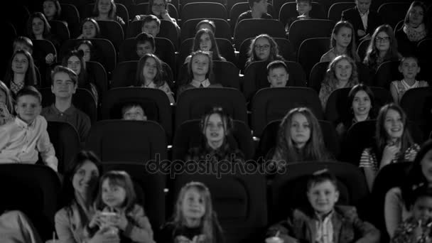 Happy children in the cinema looking a cartoon. Black and white picture.