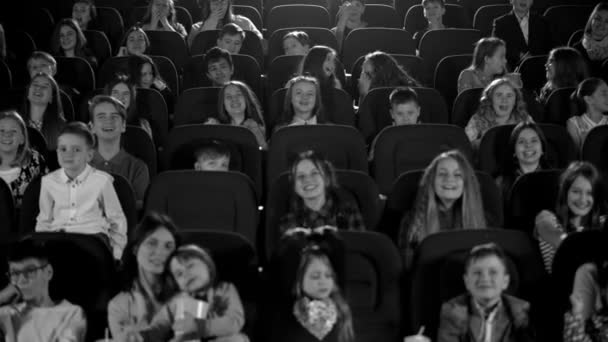 Happy children in the cinema looking a very funny cartoon and make phone flashes. Black and white shot.