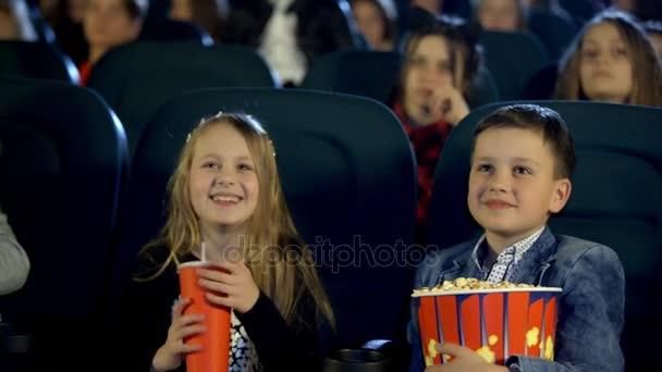 kleiner Junge und seine Freunde essen Popcorn und schauen begeistert einen Film im Kino,