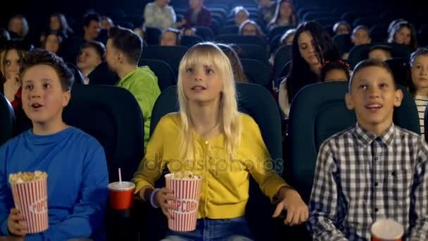 Kinder im Kino, die sehr lustig animierten Zeichentrickfilm. sie essen Popcorn und trinken Cola.