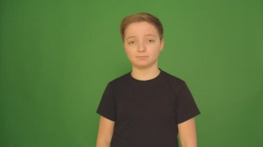 A beautiful boy shows different emotions on a green background. Camera in 4K.
