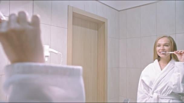 Junge Frau putzt sich im Bad die Zähne, schaut in den Spiegel, genießt gute Mundhygiene, bereitet sich auf Snowboarden vor