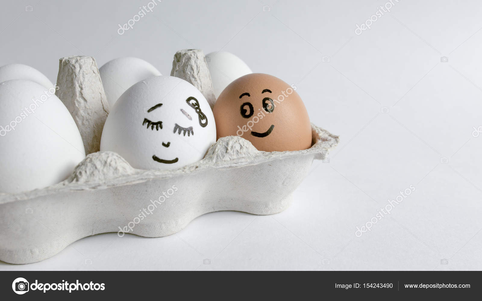 Eggs with funny faces in the package on a white background