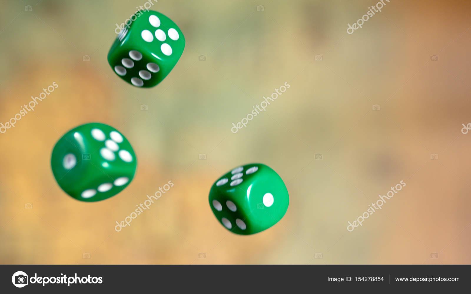 Einige rollende grüne Würfel fallen auf einem Tisch mit Brettspiel ...