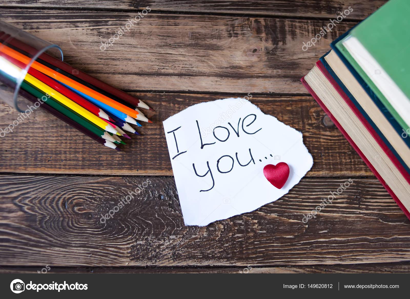 Libros sobre la mesa de madera, una nota con el corazón, lápices de ...