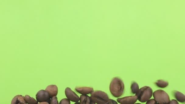 Fallenden Bohnen Kaffee auf einem Haufen von Kaffeebohnen auf einem grünen Bildschirm