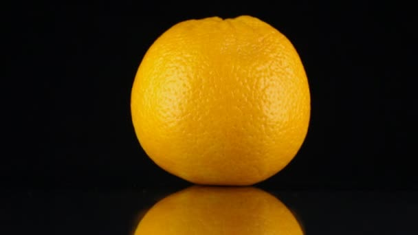 Rotating orange and its reflection on a black background.