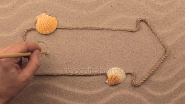 Sny nápis napsaný rukou v písku, ukazatel z lana