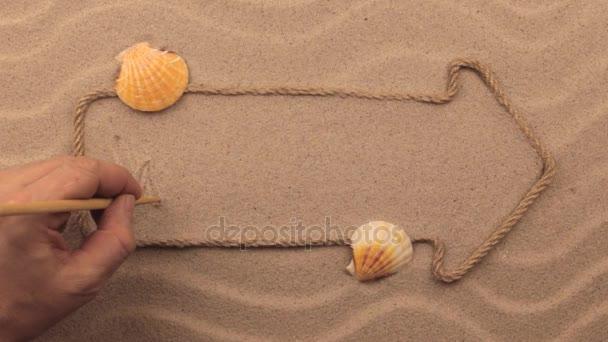 Úvodní nápis napsán rukou v písku, ukazatel z lana