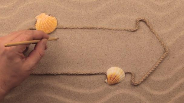 Čas nápis napsaný rukou v písku, ukazatel z lana