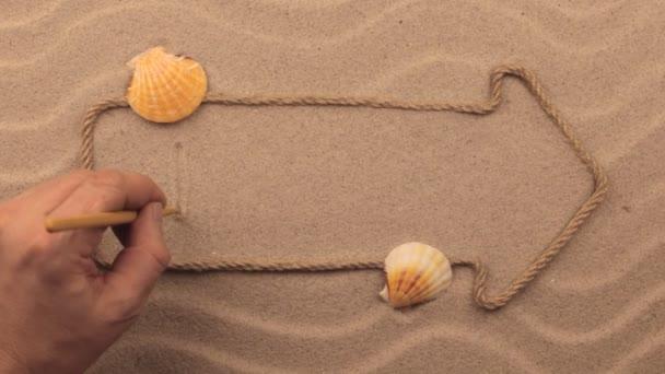 Láska nápis napsaný rukou v písku, ukazatel z lana