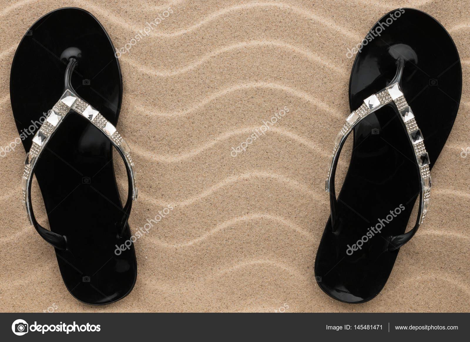 Par de sandalias de playa negra en pedrería están parados en la ...