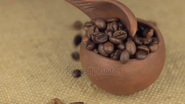 Ruka s lžící nalít kávu obilí z rotující hliněný hrnec