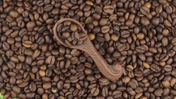 Rotation and zoom of coffee in a clay spoon lying on the background of coffee beans.