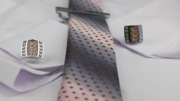 Dolly lövés. Közeli csomózott rózsaszín nyakkendő, mandzsettagombokat, és a fehér ing nyakkendő-klip.