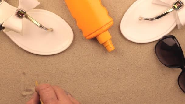 Lavrotto, nápis napsaný rukou na písku a mezi plážové doplňky. Znamení a symbol rekreace.