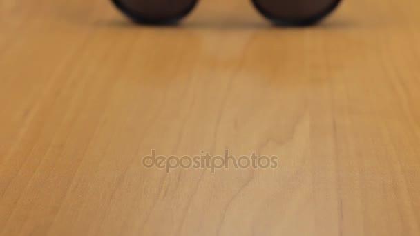 Stylové černé sluneční brýle ležet na dřevěnou podlahu. Dolly zastřelil
